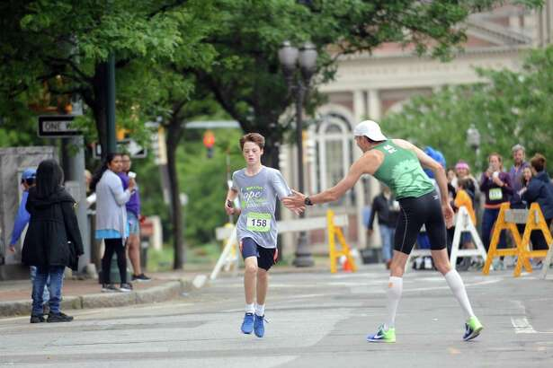 5K winner David Guzik of Fairfield, right, high-fives 15-year-old runner Tucker Healy as he reaches the final stretch of the 23rd annual Hope in Motion Walk & Run, hosted by Stamford Health's Bennett Cancer Center, at Columbus Park in downtown Stamford on Sunday.