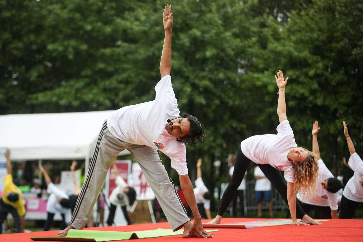 Vishwarup Nanjundappa, an SVYASA yoga instructor, left, and Lindsey Law, Pralaya Yoga instructor, right, lead the audience through a yoga practice routine during the International Yoga Day celebration on Saturday, June 24, 2017, at Town Green Park.