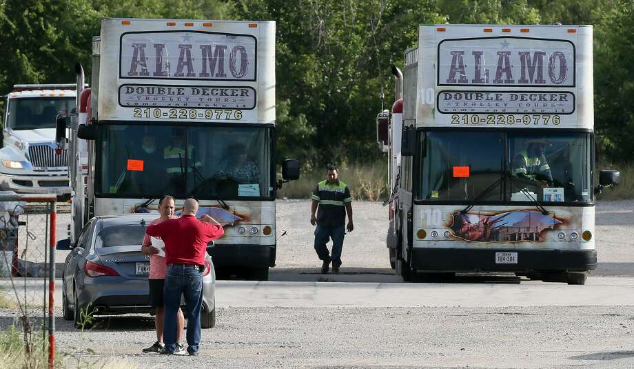 Edward Torres (left) owner of San Antonio tour operator City Tours Inc., talks to tax collection manager John Fry as Bexar County officials prepare to seize doube-decker tour buses and other vehicles at 3831 N. Foster Road on Friday. The buses were seized because City Tours has not paid personal property taxes from 2015 through 2017. Photo: Marvin Pfeiffer /San Antonio Express-News / Express-News 2018
