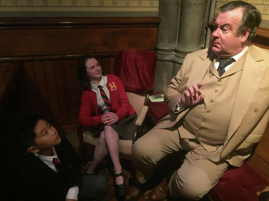 Johnson Flucker as Oscar Wilde is disconcerted by the presence of Emma Martin Mooney and Jaden Lee of the Trinity Church on the Green choirs in a recent visit. Photo: Trinity Church / Contributed Photo