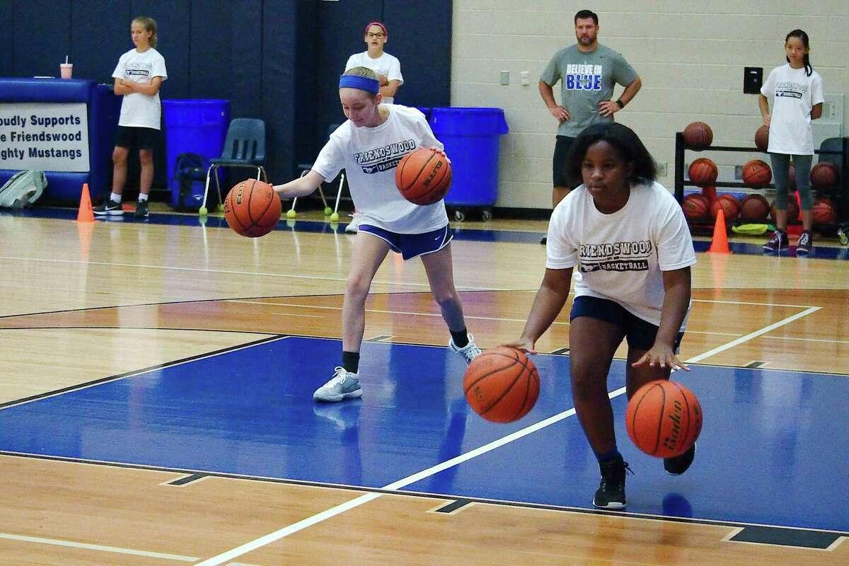 Samantha McFadden and Savanah Bolden participate in a dribbling drill at Friendswood summer basketball camp Thursday, Jun. 7.