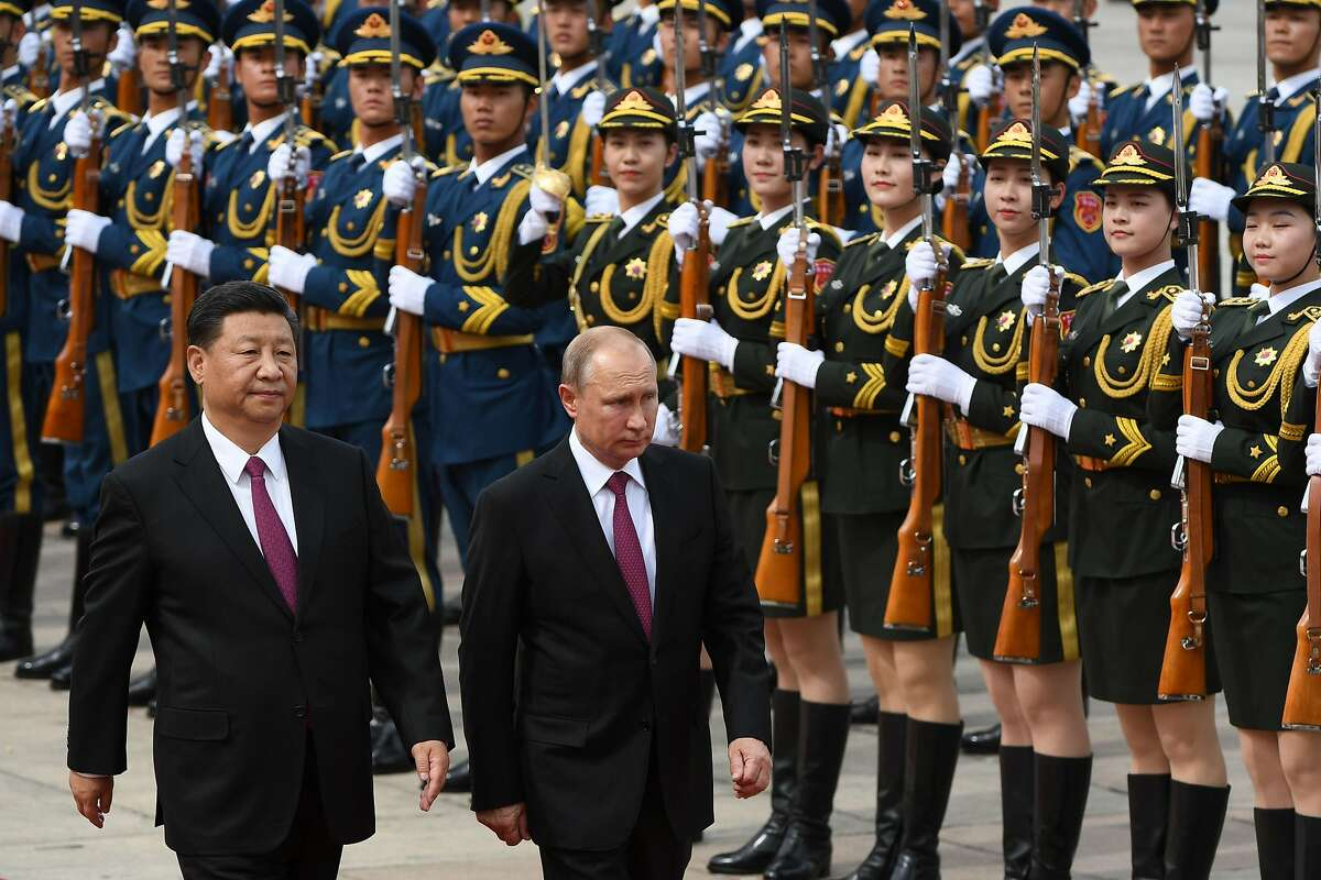 TOPSHOT - Russia's President Vladimir Putin (C) reviews a military honour guard with Chinese President Xi Jinping (L) during a welcoming ceremony outside the Great Hall of the People in Beijing on June 8, 2018. Putin arrived on June 8 for a state visit to China and will attend the Shanghai Cooperation Organisation Leaders Summit in the eastern port city of Qingdao on June 9-10. / AFP PHOTO / POOL / Greg BAKERGREG BAKER/AFP/Getty Images