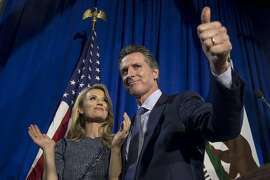 Gavin Newsom, Democratic candidate for governor of California, gives a thumbs-up as his wife Jennifer Siebel Newsom, looks on during a primary election watch party in San Francisco, California, U.S., on Tuesday, June 5, 2018. Lieutenant Governor�Newsom�and Republican businessman John Cox won the most votes in California�s gubernatorial primary, advancing to a general election that will test the state�s position as leader of the resistance to President�Donald Trump. Photographer: David Paul Morris/Bloomberg