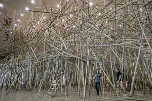 """Mike Starn, right, and his brother Doug Starn, second from right, work within their installation, """"Big Bambu: This Thing Called Life,"""" at the Museum of Fine Arts, Houston."""