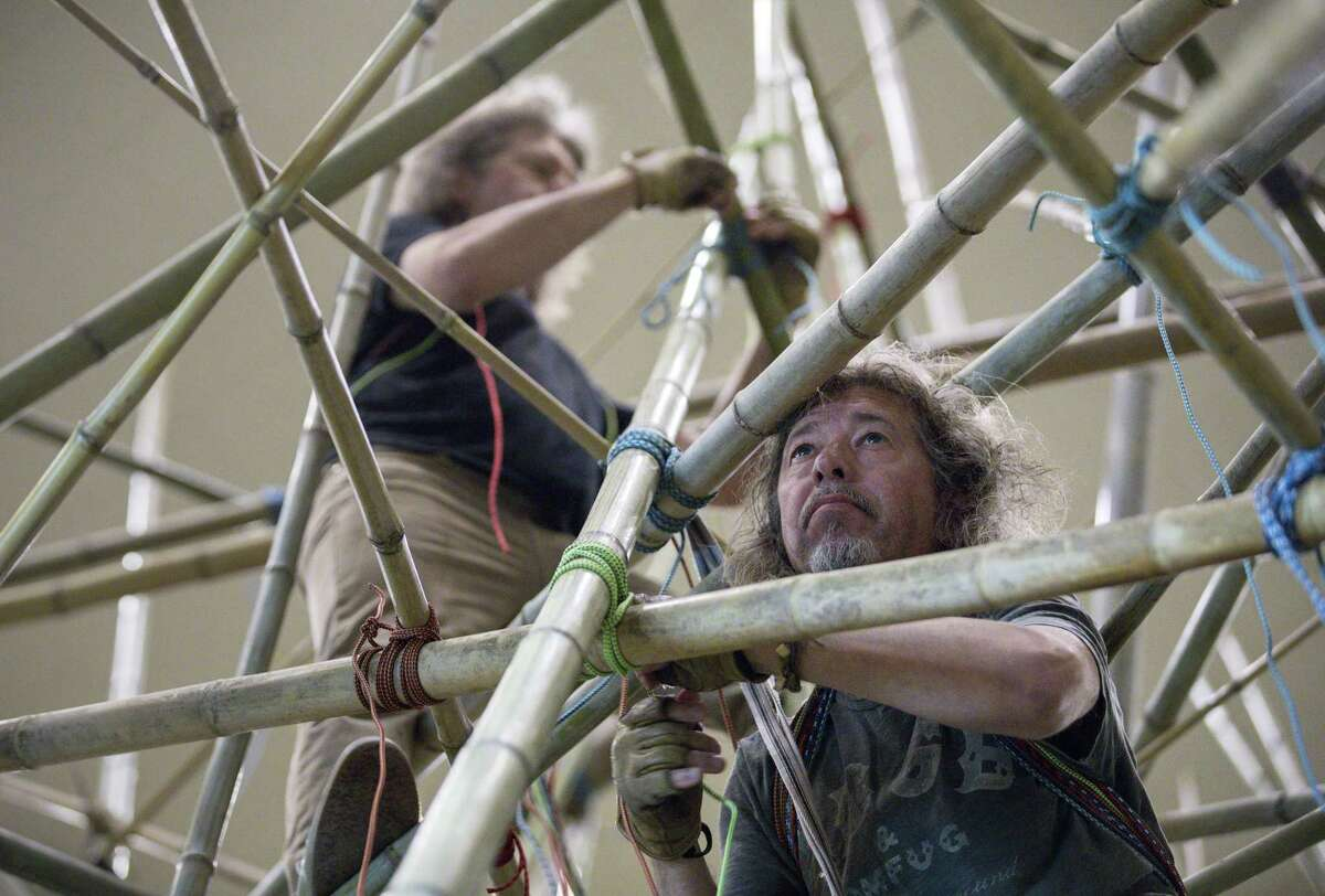Doug Starn, right, and his brother Mike, rear, work within their installation,