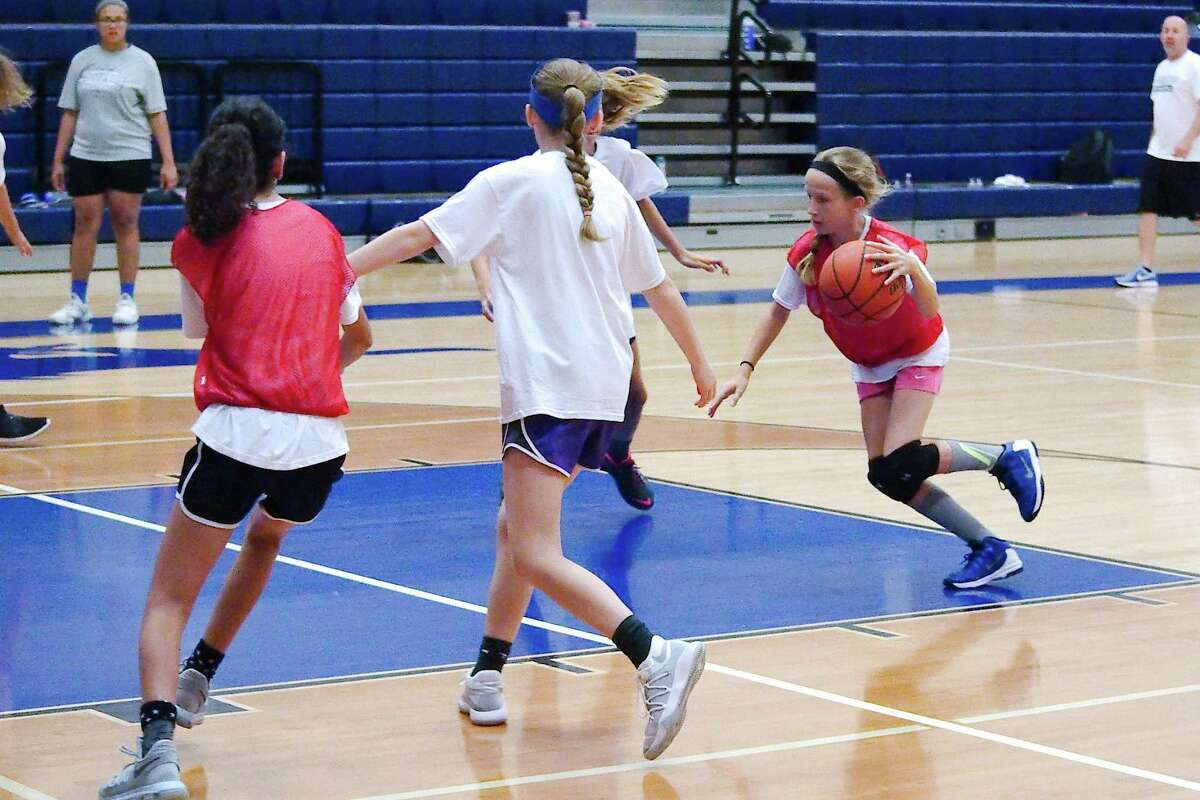 Emma Slaton drives to the basket as she and her teammates participate in a 3-on-3 drill at Friendswood summer basketball camp Thursday, June 7.