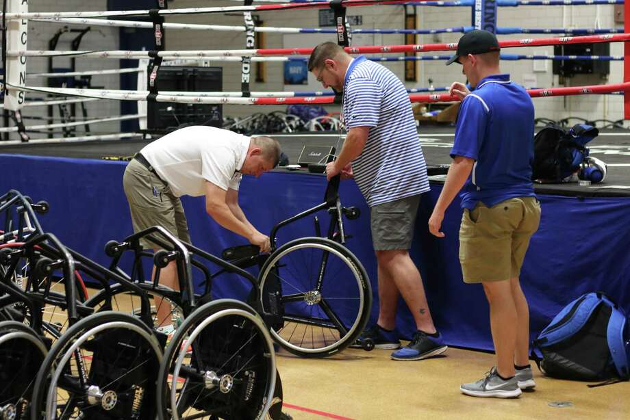 "Veteran Jarrett Jongema, 44, a contractor for the Air Force, of San Antonio, Texas, works on an adaptive sports wheelchair with the help of Derrick Lepper, 47, a Wounded Warrior adaptive sports coordinator, of Denver, Colorado, at the Warrior Games on Friday, June 1, 2018, at the Air Force Academy near Colorado Springs, Colorado. Officer Ian Clemens, 25, a member of the Air Force, of San Antonio, Texas, chats with them as Jongema works. In 2004, Jongema coded out eight times after a car bomber drove into the front of his truck while he was providing security in Baghdad. He was awarded two Purple Hearts, which he dedicated to the two men that died in the blast. After his injury, he could have stopped working completely, but instead he works support operations at the Warrior Games 14-16 hours a day. ""I don't need the Warrior Games from a competitive standpoint,"" Jongema says. ""I'm happy to see all the smiles we get."" (Photo/Miranda Daniel, Grady Sports Bureau) Photo: MIRANDA DANIEL, Staff / Miranda Daniel/GRADY SPORTS BUREAU / © 2018 Miranda Daniel"