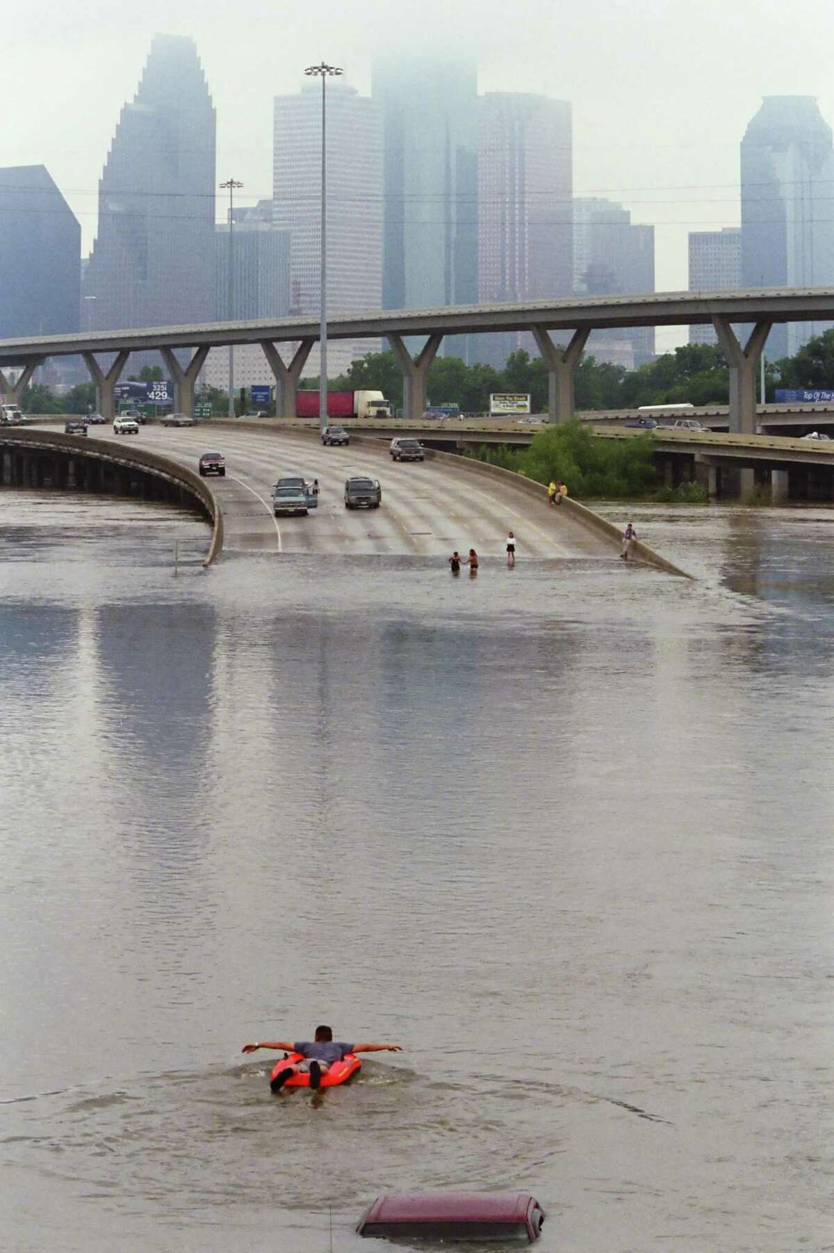 A man in a rubber boat paddles through flood waters caused by the remnants of Tropical Storm Allison covering I-45 north of downtown Houston Saturday, on June 9, 2001.