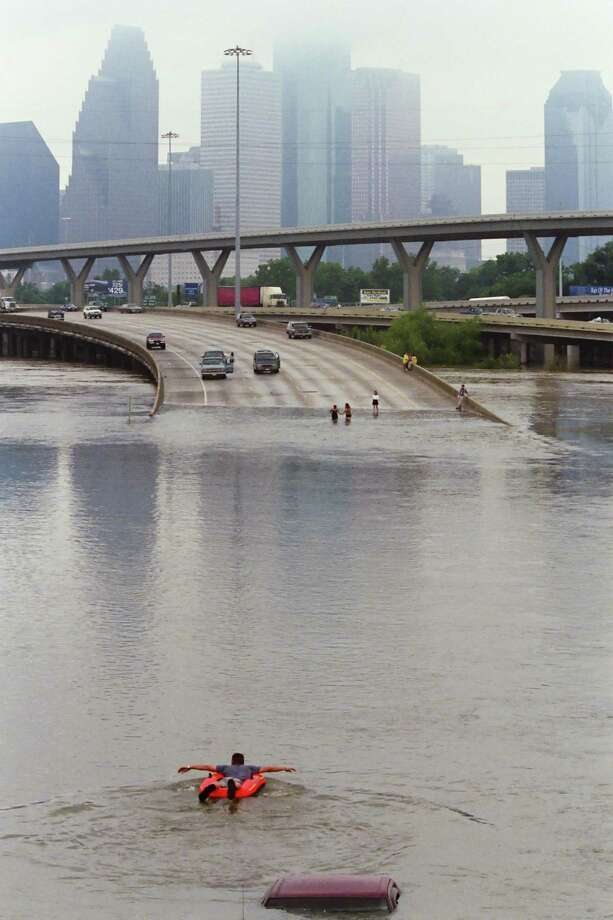 A man in a rubber boat paddles through flood waters caused by the remnants of Tropical Storm Allison covering I-45 north of downtown Houston Saturday, on June 9, 2001. Photo: Buster Dean, Staff / Houston Chronicle / Houston Chronicle
