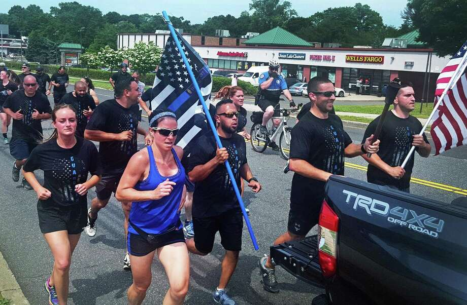 Norwalk police officers, along with state troopers and other first responders ran through Nowalk on Friday with the torch for the Connecticut Special Olympics. Photo: Thane Grauel / Hearst Connecticut Media / Connecticut Post