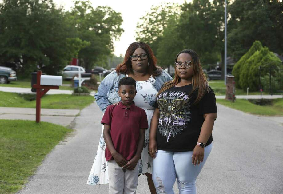 Catina Washington, 43, poses with her children Jaquavion Jackson, 10, and Jakwannai Washington, 20, near their Harvey-flooded home in East Houston on Thursday, May 3, 2018. Washington's ranch-style house took in about four feet of water. The three and Washington's 61-year-old mother, Janice Washington, evacuated their home after they waited more than 20 hours after calling 911 for help. Photo: Yi-Chin Lee / Houston Chronicle / © 2018 Houston Chronicle