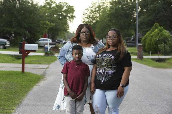 Catina Washington, 43, poses with her children Jaquavion Jackson, 10, and Jakwannai Washington, 20, near their Harvey-flooded home in East Houston on Thursday, May 3, 2018. Washington's ranch-style house took in about four feet of water. The three and Washington's 61-year-old mother, Janice Washington, evacuated their home after they waited more than 20 hours after calling 911 for help.