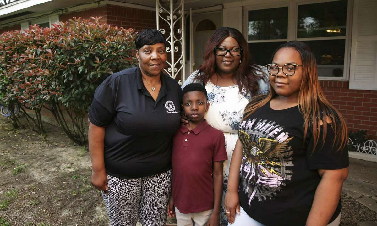Catina Washington, 43, second from right, poses for a photograph with her mother, Janice Washington, 61, and her children, Jaquavion Jackson, 10, and Jakwannai Washington, 20, in front of her Harvey flooded house in East Houston on Thursday, May 3, 2018. Washington's ranch-style house took on about four feet of water during Harvey. The family evacuated their home after they waited more than 20 hours after calling 911 for help.