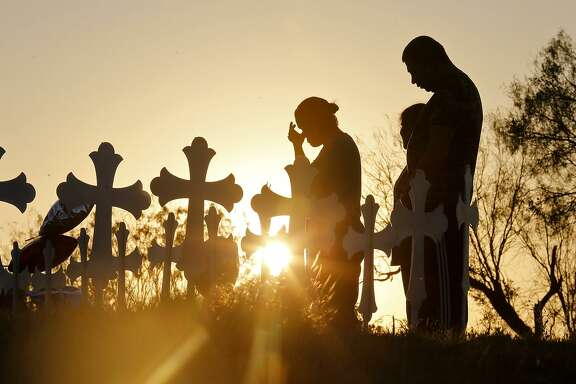 Irene (left) and Kenneth Hernandez (right) with their daughter Miranda pray, Monday Nov. 6, 2017, at the 26 crosses for those killed in the mass shooting at the First Baptist Church of Sutherland Springs.