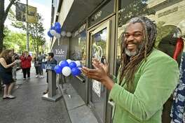 Fashion designer Neville Wisdom, right, applauds remarks by New Haven Mayor Toni Harp during a ribbon-cutting ceremony recently for his new storefront on Chapel Street, Neville Wisdom Fashions, at The Shops at Yale. The store is situated between The Juice Box and Atticus Bookstore & Cafe, and across from the Yale Art Gallery.