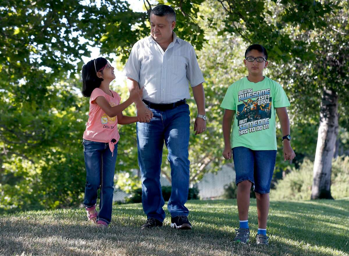 Mohanad Al-Manasser walks in the neighborhood with his daughter Najla, 7, and son Monjed, 11, in Antelope, Calif. on Friday, June 8, 2018. Al-Manasser's mother and brother are seeking refugee asylum but their case is tied up in the complicated immigration system.