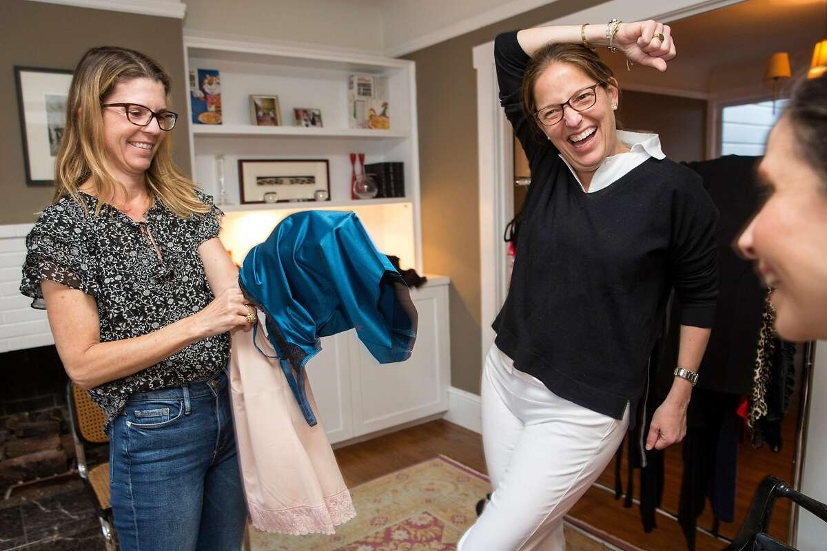Heather Howard (center), the hostess, jokes with Natasha Bradley (left) who holds a couple of Ruby Ribbon garments during�in-home demonstration in Noe Valley on Wednesday, May 30, 2018. San Francisco Calif. Ruby Ribbon is an apparel company based in Silicon Valley.
