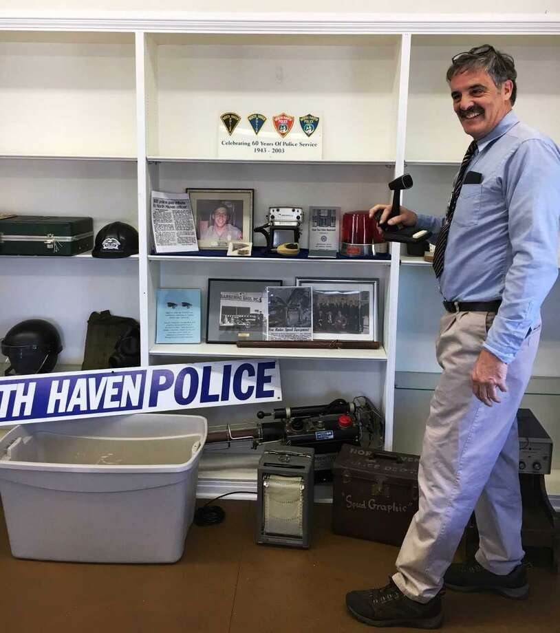 Officer Ted Stockmon, presenter of the program,  with a display of vintage police artifacts from the North Haven PD. Photo: Contributed Photo