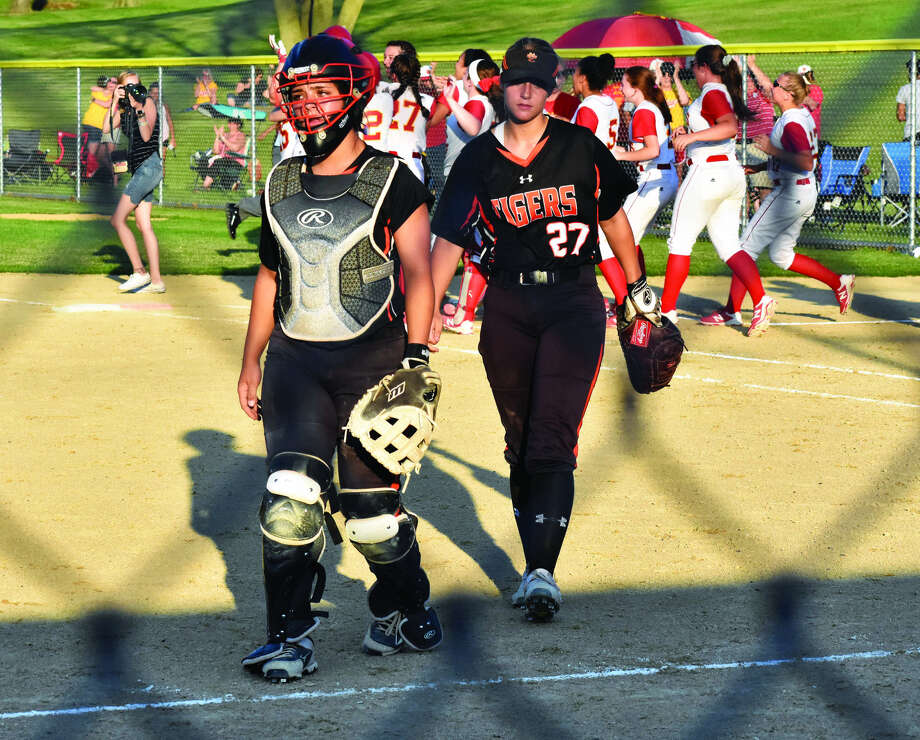 Edwardsville's Taryn Brown, left, and Meghan Gorniak walk off the field as Rock Island celebrates its first sectional championship in Pekin.