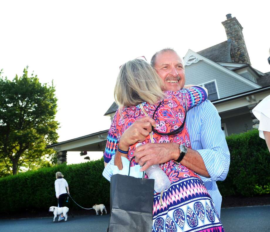 Glenn Yanicky, a mailman in Old Greenwich for 34 years, gets a hug during a retirement party for him held by members of the Lucas Point Association beach community Thursday. Photo: Bob Luckey Jr. / Hearst Connecticut Media / Greenwich Time