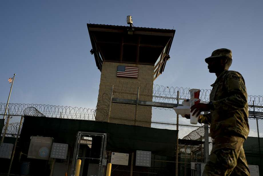 A U.S. task force member walks past the Camp VI detention facility at the Guantanamo Bay U.S. Naval Base in Cuba on Tuesday. The Obama administration had sought to close the facility. Photo: Ramon Espinosa / Associated Press