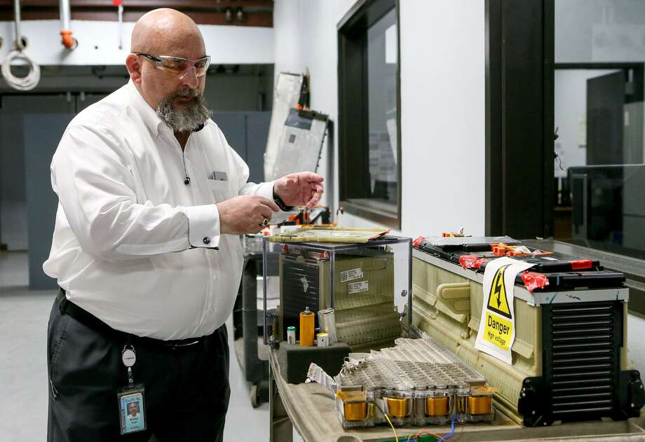 Mickey Argo, Assistant Manager of Vehicle Electrification and Energy Storage Technology at Southwest Research Institute, shows lithium-ion batteries used by a Tesla (lower center), Chevrolet Volt (right) automobiles in their new battery testing facility on Wednesday, June 6, 2018. MARVIN PFEIFFER/mpfeiffer@express-news.net Photo: Photos By Marvin Pfeiffer /San Antonio Express-News / Express-News 2018