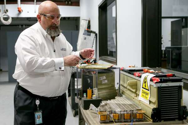 Mickey Argo, Assistant Manager of Vehicle Electrification and Energy Storage Technology at Southwest Research Institute, shows lithium-ion batteries used by a Tesla (lower center), Chevrolet Volt (right) automobiles in their new battery testing facility on Wednesday, June 6, 2018. MARVIN PFEIFFER/mpfeiffer@express-news.net