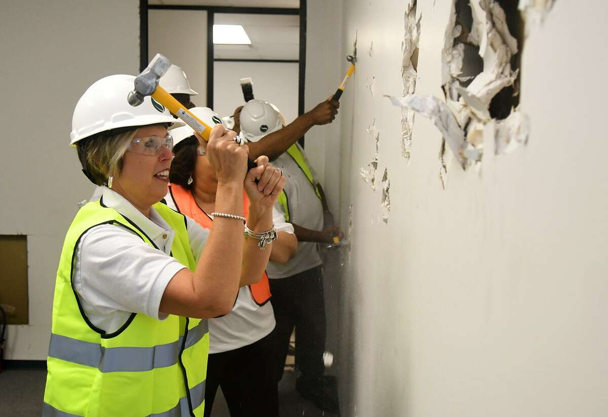 Jana Gonzales, left, joined by all of her fellow Spring Independent School District Board of Trustees members, takes her turn with a hammer during the ceremonial wall demolishment as renovations began on the new Police Command Center, being built under the 2016 bond program, at the Lockhaven facility on June 7, 2018. The event was designed to highlight upcoming construction work at the 41,644 square-foot building which will feature the new Police Command Center and the district's Tax, Technology and Risk Management offices. (Jerry Baker/For the Chronicle)