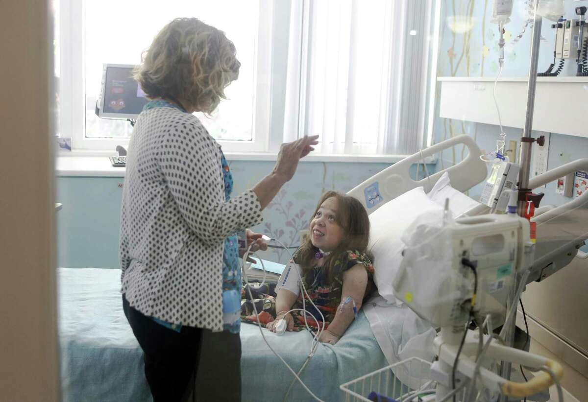 Isabel Bueso receives her weekly drug treatment from nurse Diane Oviatt at UCSF Benioff Children's Hospital on Friday, a day before her Cal State graduation.