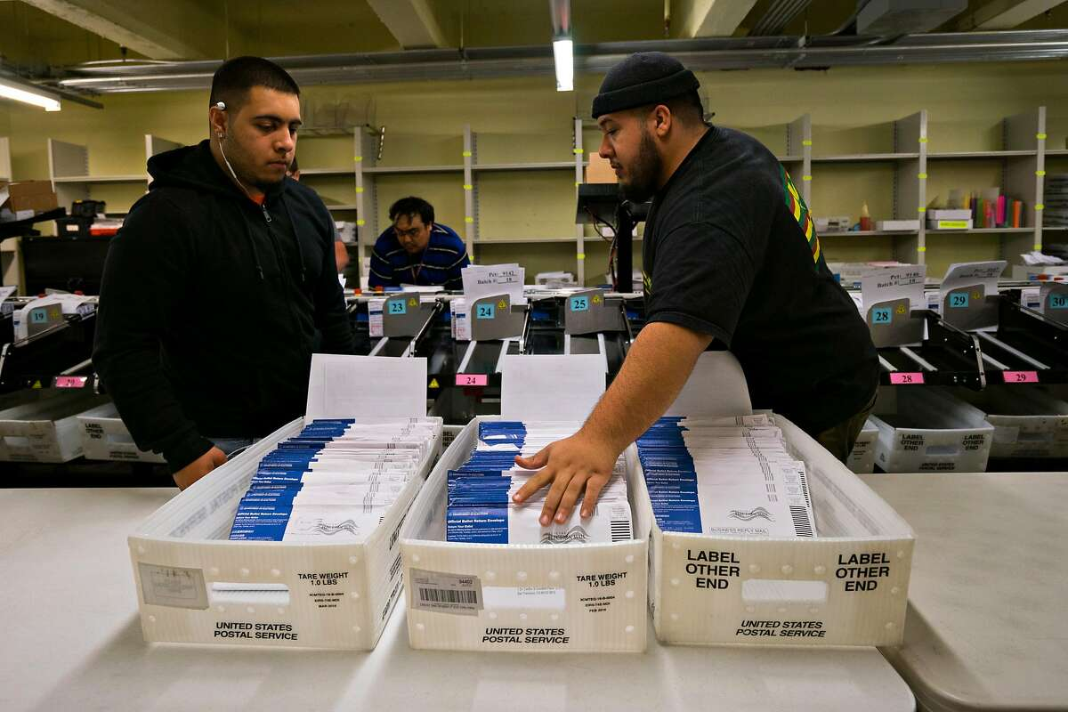 Damian Buoni (left) and Dominic Buoni sort mail-in ballots for the mayoral election at City Hall in San Francisco, Calif. on Friday, June 8, 2018.
