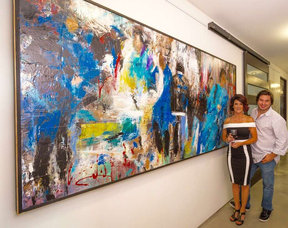 """Kellie Nedd (left) and Chris Carrillo of South Woodlands Art Gallery (SWAG) in front of """"Distracted"""" by Nedd, 8-foot x 4-foot, mixed media on wood."""