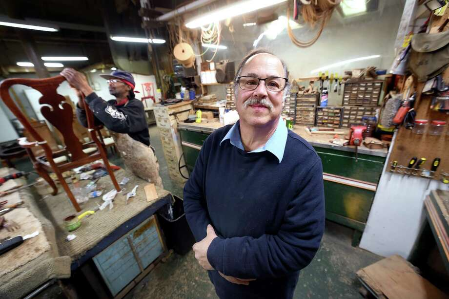 Barry Radin (center), owner of The Furniture Doctor, in his store on Derby Avenue in New Haven. Working on a chair at left is Leon Henderson, who has worked at the business for 33 years. Photo: Arnold Gold / Hearst Connecticut Media / New Haven Register