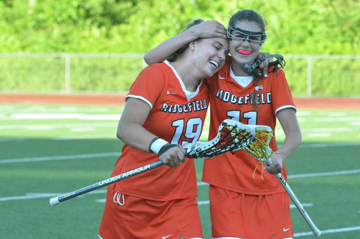 Ridgefield's Caroline Curnal (19) scores the winning goal and is hugged by Maeve Tobin after the overtime win against Cheshire in Girls lacrosse Class L semifinal game on Tuesday in Norwalk.