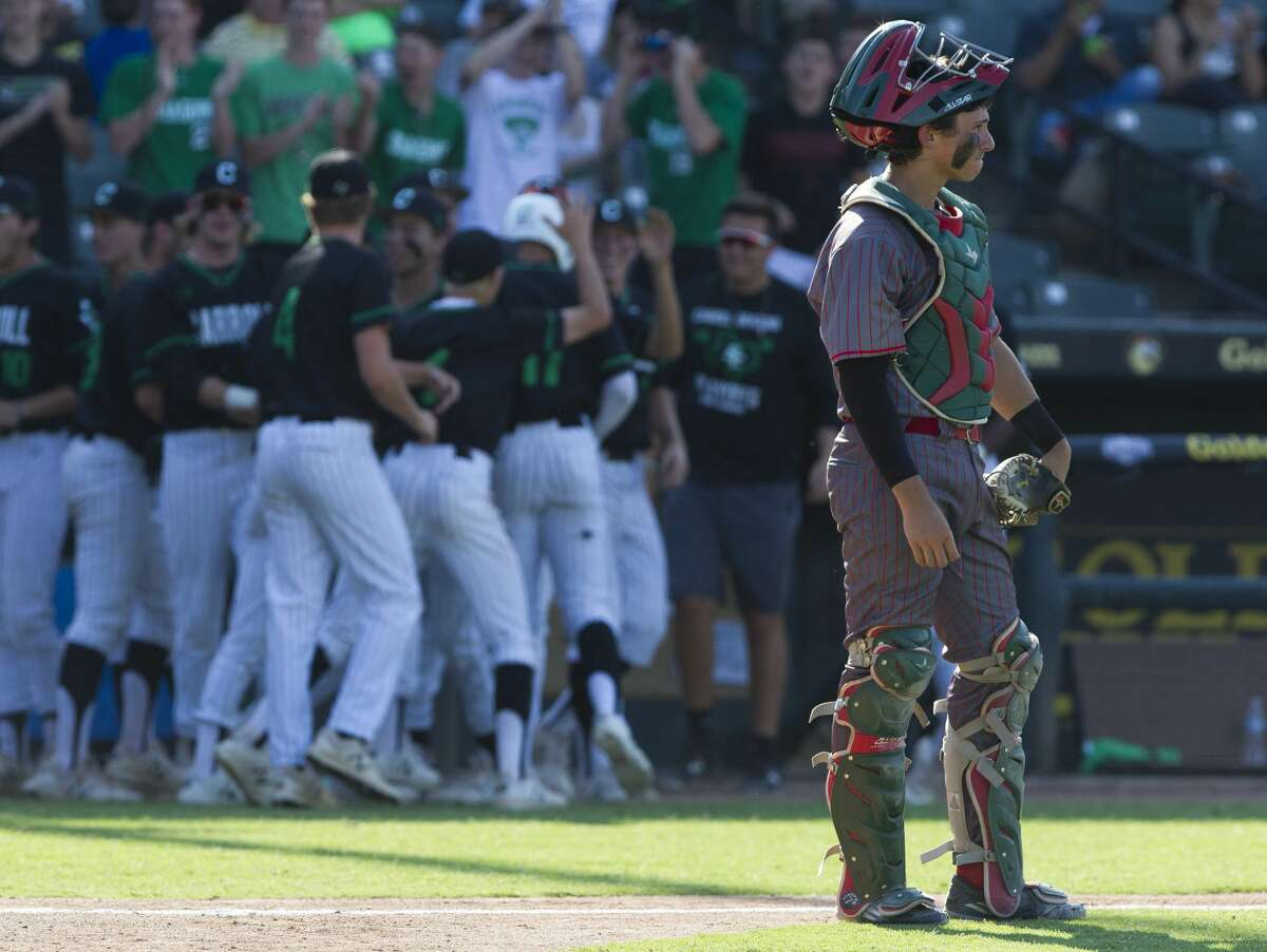 The Woodlands catcher Drew Romo watches as Southlake Carroll's Jorge Figueroa reacts after his 2-run double in the sixth inning of a Class 6A state semifinal game during the UIL State Baseball Championships at Dell Diamond on Friday, June 8, 2018, in Round Rock.