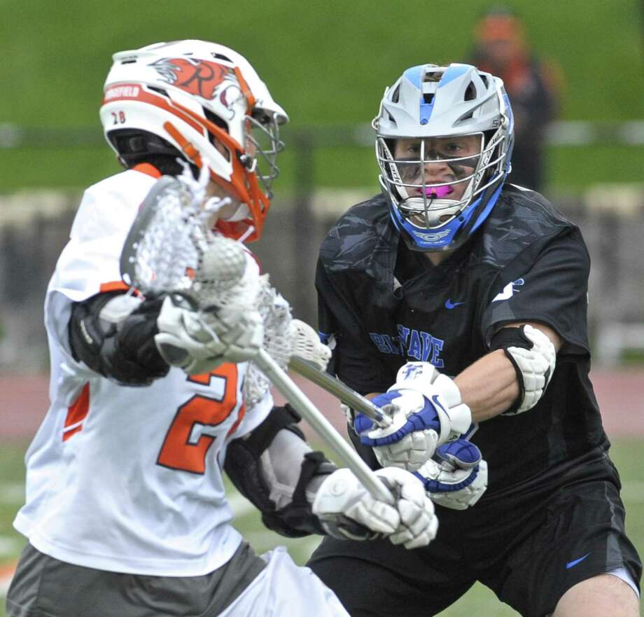 Darien's Matt Gould (49) pokes at Ridgefield's Dawson Muller (28) in the boys lacrosse game between Darien and Ridgefield high schools, Saturday afternoon, May 12, 2018, at Ridgefield High School, Ridgefield, Conn. Photo: H John Voorhees III / Hearst Connecticut Media / The News-Times
