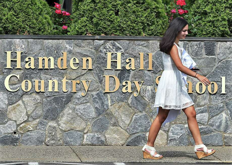 Sophia Lawder-Gill of New Haven carries her cap and gown on her way to the Taylor Performing Arts Center for commencement exercises at Hamden Hall Country Day School Friday. Photo: Catherine Avalone / Hearst Connecticut Media / New Haven Register