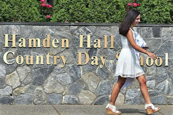 Sophia Lawder-Gill of New Haven carries her cap and gown on her way to the Taylor Performing Arts Center for commencement exercises at Hamden Hall Country Day School Friday.