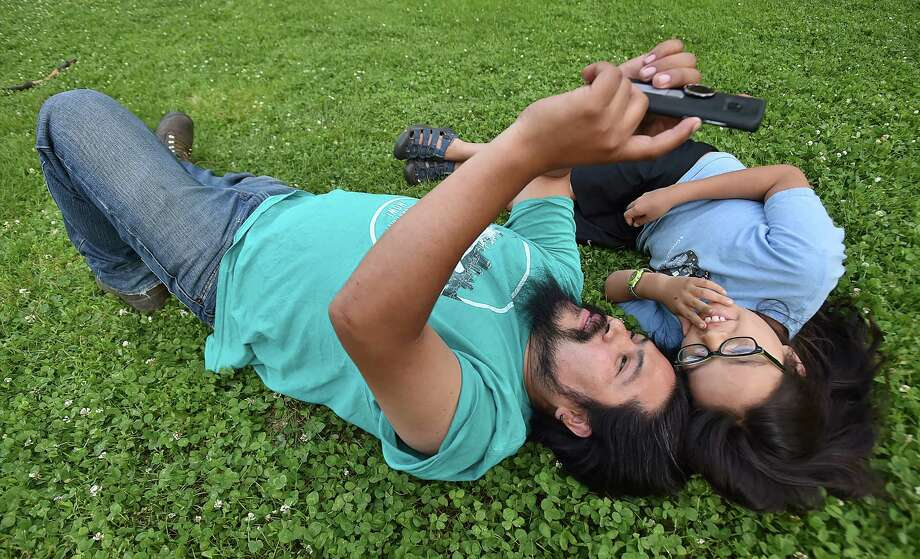 """New Haven resident Erick Sarmiento, emigrated from Mexico and his daughter Kai Sarmiento take a selfie at the opening of """"WE ARE: A Nation of Immigrants — New Haven"""" by photographer Joe Standart, Friday, June 8 on the New Haven Green. The Sarmientos are featured in the exhibit on the Green. Photo: Catherine Avalone, Hearst Connecticut Media / New Haven Register"""