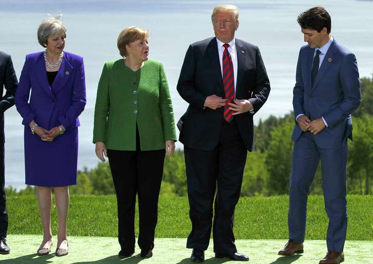 Theresa May, U.K. prime minister, from left, Angela Merkel, Germany's chancellor, U.S. President Donald Trump, and Justin Trudeau, Canada's prime minister, get in place for a family photograph during the Group of Seven (G7) Leaders Summit in La Malbaie, Quebec, Canada, on Friday, June 8, 2018.