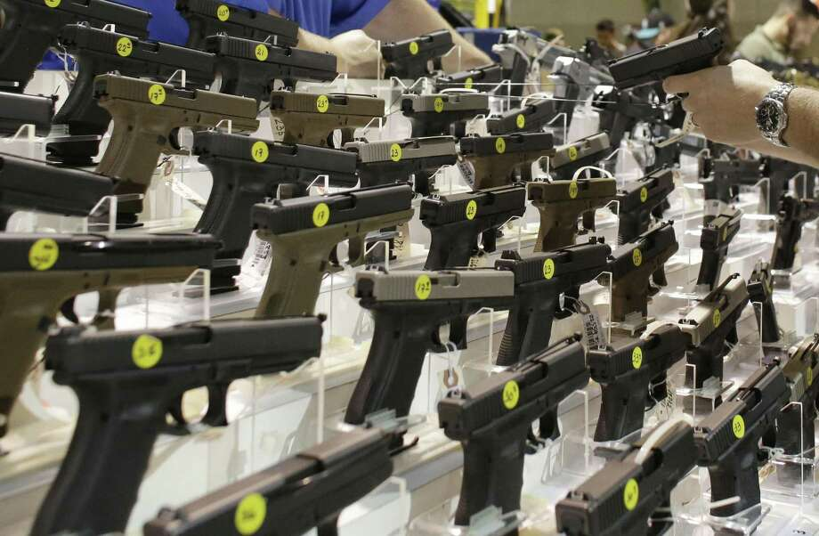 A customer looks at a pistol at a vendor's display during a 2016 gun show in Miami. Photo: Lynne Sladky / Associated Press / AP