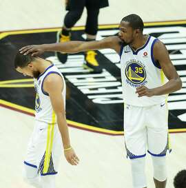 Golden State Warriors' Stephen Curry gets a head pat from Kevin Durant in the third quarter during game 4 of The NBA Finals between the Golden State Warriors and the Cleveland Cavaliers at Quicken Loans Arena on Friday, June 8, 2018 in Cleveland, Ohio.