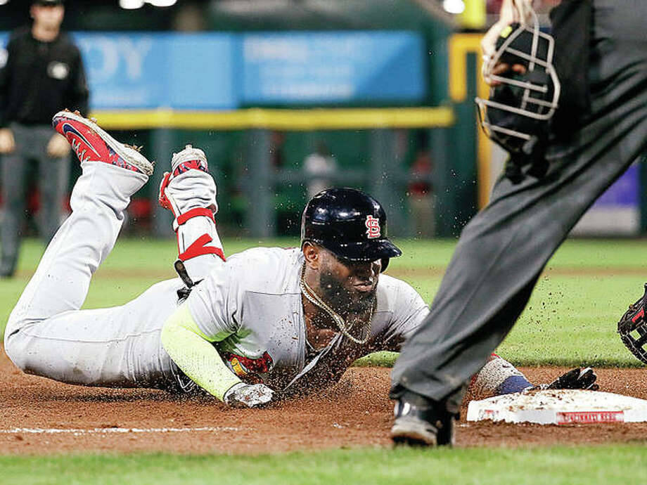 The Cardinals' Marcell Ozuna slides into third on a triple off Cincinnati Reds relief pitcher Michael Lorenzen in the eighth inning of Friday night's game in Cincinnati. Photo:       AP