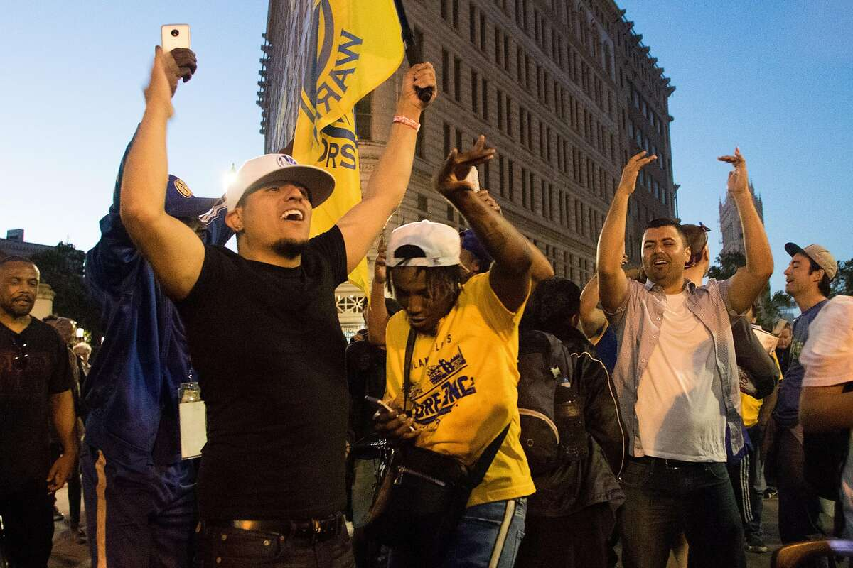 Golden State Warriors fans celebrate their team's victory in the NBA Finals at 14th and Broadway in Downtown Oakland, Calif. on Friday, June 8, 2018.