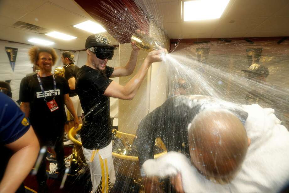 Klay Thompson sprays champagne on team staff members in the locker room after the Golden State Warriors defeated the Cleveland Cavaliers in Game 4 of the NBA Finals at Quicken Loans Arena in Cleveland, Ohio, on Friday, June 8, 2018. The Warriors won 108-85 to win the the 2018 NBA Championship. Photo: Carlos Avila Gonzalez, The Chronicle