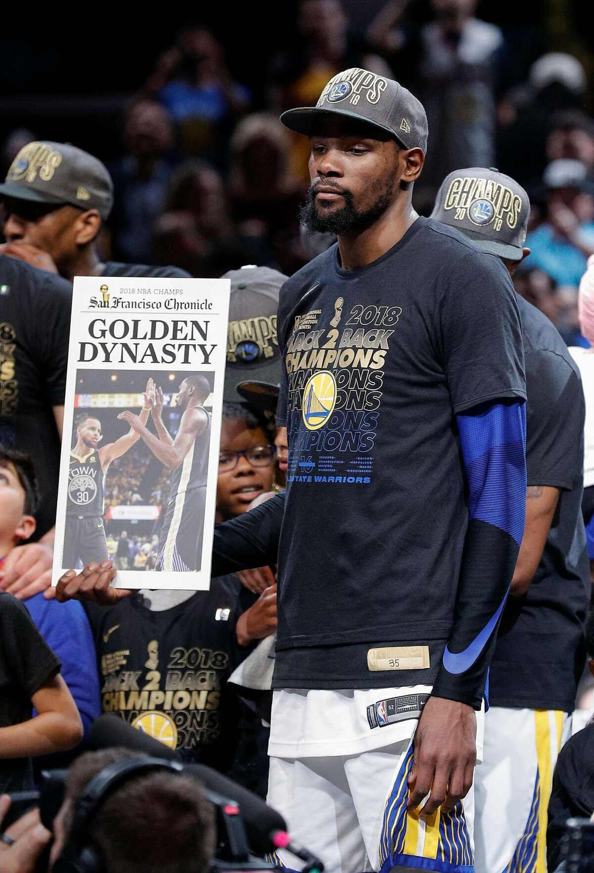 The Golden State Warriors' Kevin Durant holds up a Chronicle front page after their 108 to 85 victory over the Cleveland Cavaliers in game 4 of The NBA Finals between the Golden State Warriors and the Cleveland Cavaliers at Oracle Arena on Friday, June 8, 2018 in Cleveland, Ohio.