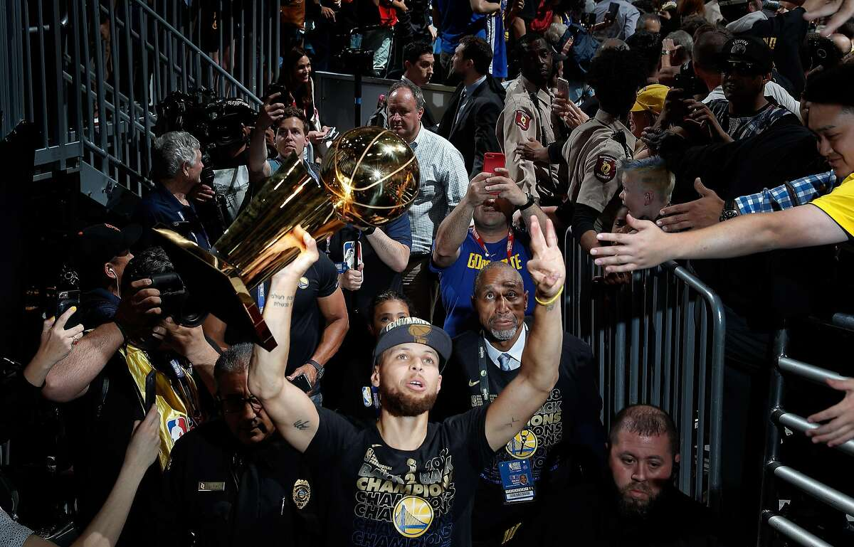 Stephen Curry (30) walks off the arena floor with the Larry O'Brien Trophy after the Golden State Warriors defeated the Cleveland Cavaliers in Game 4 of the NBA Finals at Quicken Loans Arena in Cleveland, Ohio, on Friday, June 8, 2018. The Warriors won 108-85 to win the the 2018 NBA Championship.