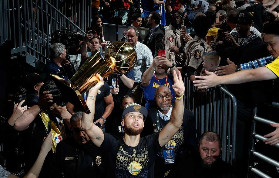 Stephen Curry (30) walks off the arena floor with the Larry O'Brien Trophy after the Golden State Warriors defeated the Cleveland Cavaliers in Game 4 of the NBA Finals at Quicken Loans Arena in Cleveland, Ohio, on Friday, June 8, 2018. The Warriors won 108-85 to win the the 2018 NBA Championship. Photo: Carlos Avila Gonzalez / The Chronicle