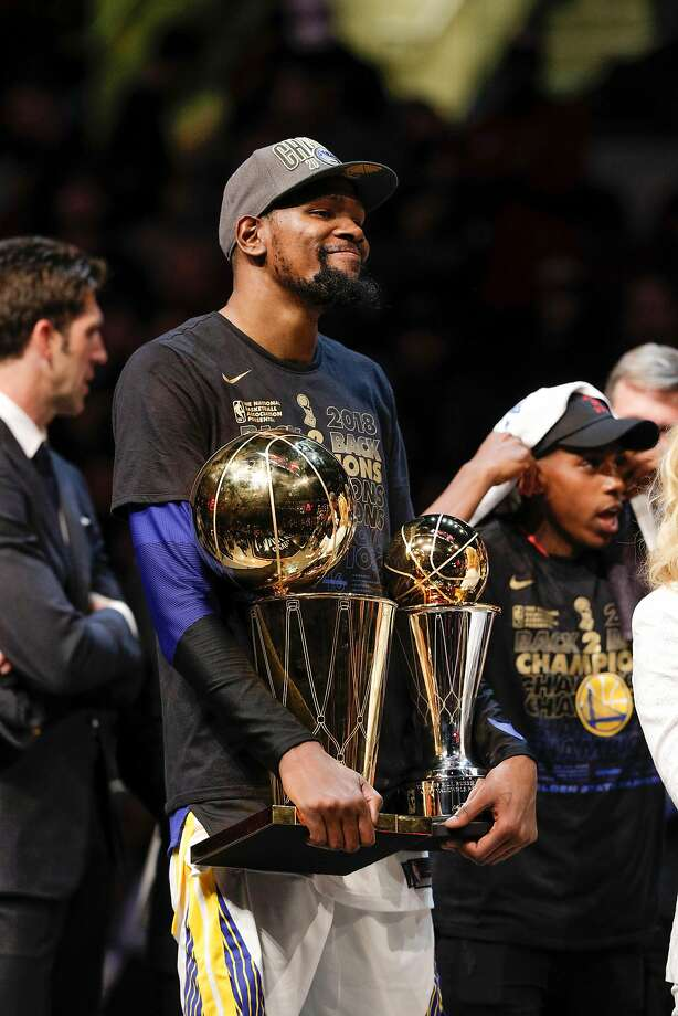 Golden State Warriors' Kevin Durant holds the the Larry O�Brien NBA Championship Trophy and The Bill Russell MVP Award after game 4 of The NBA Finals between the Golden State Warriors and the Cleveland Cavaliers at Oracle Arena on Friday, June 8, 2018 in Cleveland, Ohio. Photo: Carlos Avila Gonzalez, The Chronicle