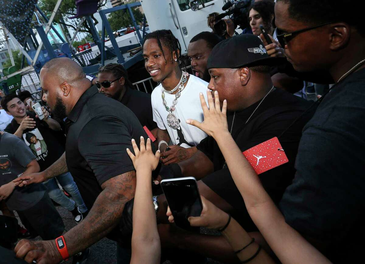 Rapper Travis Scott is swarmed by fans as he arrives at his block party at Root Memorial Square on Friday, June 8, 2018, in Houston.