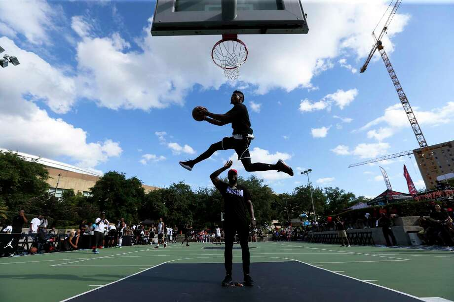 """Issac """"Sir Issac"""" White jumps over and picks up the basketball for a dunk during warm up of a basketball game at rapper Travis Scott's block party at Root Memorial Square on Friday, June 8, 2018, in Houston. Photo: Yi-Chin Lee, Houston Chronicle / © 2018 Houston Chronicle"""